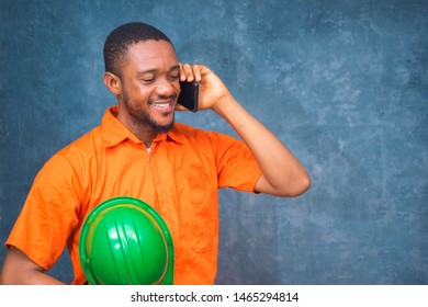 an handsome Nigerian engineer calling a business call with his phone