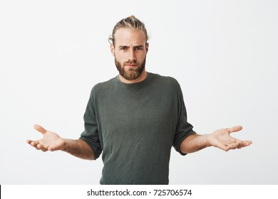 Handsome nordic man with beard and stylish hairdo spreads hands with cynical and mean expression when somebody pushed him on street.