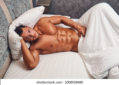 A handsome nude man lying in a bed.