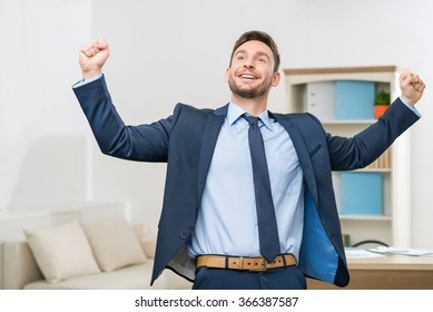 Handsome office worker celebrating victory