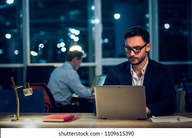 Handsome office worker typing on laptop. Good looking man with beard and glasses working behind computer late at night in office with big glass windows.