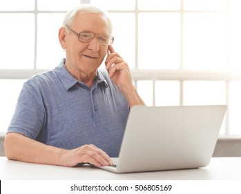 Handsome old businessman in casual clothes and eyeglasses is talking on the mobile phone, using a laptop and smiling while sitting in his office