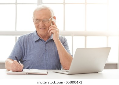 Handsome old businessman in casual clothes and eyeglasses is talking on the mobile phone, making notes and smiling while sitting in his office