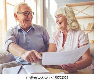 Handsome old man and beautiful woman are discussing documents, looking at each other and laughing while sitting on couch at home