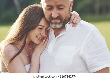 Handsome old man and beautiful young girl are hugging, daughter and her old dad spend time together outdoors.