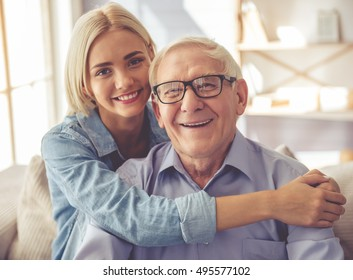 Handsome old man and beautiful young girl are hugging, looking at camera and smiling while sitting on couch at home