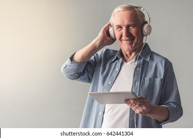 Handsome old man in casual wear and headphones is listening to music using a digital tablet and smiling, on gray background