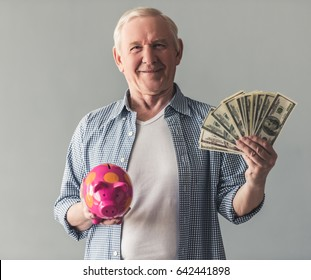 Handsome old man in casual wear is holding a piggy bank and money, looking at camera and smiling, on gray background