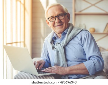 Handsome old man dressed in smart casual style and eyeglasses is using a laptop, looking at camera and smiling while sitting on couch at home