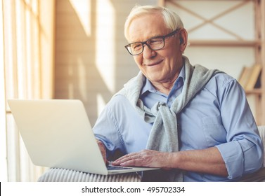 Handsome old man dressed in smart casual style and eyeglasses is using a laptop and smiling while sitting on couch at home