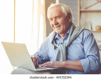 Handsome old man dressed in smart casual style is using a laptop and smiling while sitting on couch at home