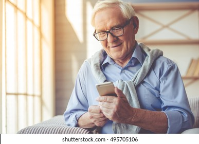 Handsome old man dressed in smart casual style and eyeglasses is using a smartphone and smiling while sitting on couch at home