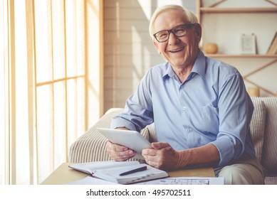 Handsome old man in eyeglasses is using a digital tablet, looking at camera and smiling while working at home