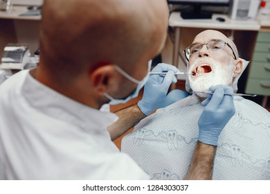 Handsome old man talking to the dendist. Two man in the dentist's office