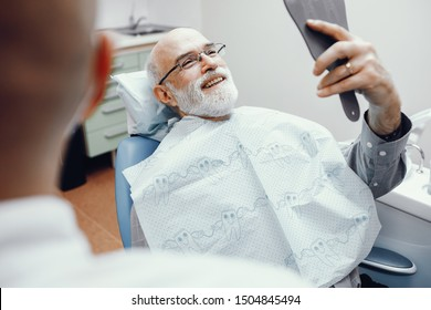 Handsome old man talking to the dendist. Two men in the dentist's office. Grandfather looking into the mirror on his teeth