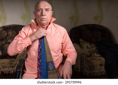 Handsome old man trying on several ties