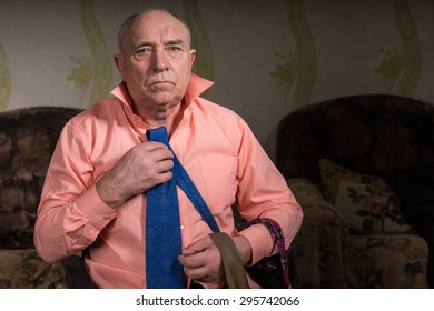 Handsome old sad man is trying on a beautiful blue tie sitting in his living room wearing a stylish shirt and some ties on his hand
