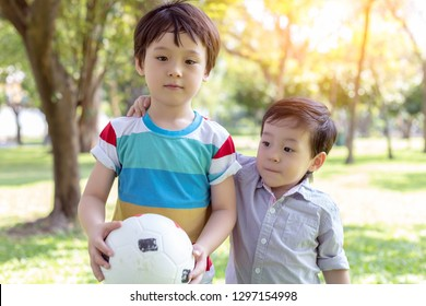 Handsome older brother holding ball and ready for playing in the park with younger brother. Little boy is always accompanied with his big brother and they always playing together. They love each other