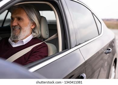 Handsome older gentleman is enjoying his drive in his new car