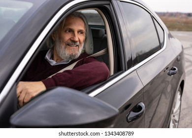 Handsome older man driving his car looking trough the window