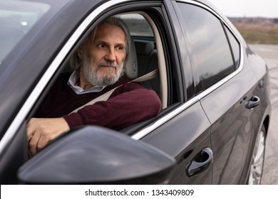 Handsome older man is driving his car and looking trough the window