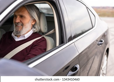 Handsome older man is driving his car
