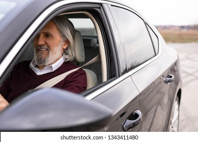 Handsome older man is driving his car and enjoying his ride