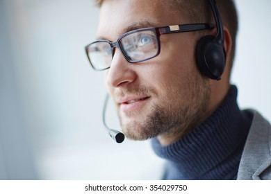 Handsome operator with headphones and mike working online