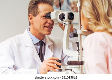 Handsome ophthalmologist examining beautiful woman's eyes with modern equipment
