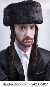 Handsome Orthodox Jewish man Hasidim with a large fur hat and side locks in a black suit