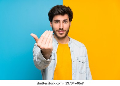 Handsome over isolated colorful background inviting to come with hand. Happy that you came