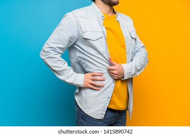 Handsome over isolated colorful background suffering from backache for having made an effort