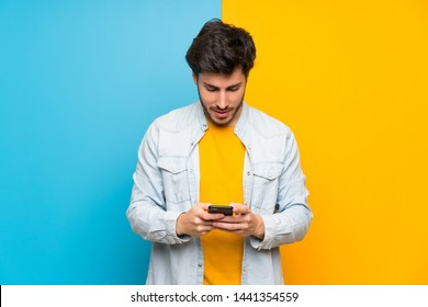 Handsome over isolated colorful background sending a message with the mobile