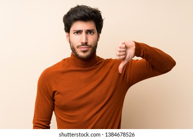 Handsome over isolated wall showing thumb down sign