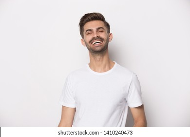 Handsome overjoyed millennial guy wearing white t-shirt laughing feeling good having great mood standing isolated on studio background, happy person, rejoice hilarious man posing indoors concept image