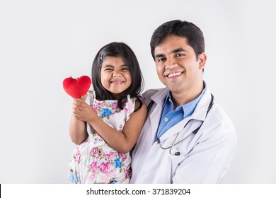 handsome paediatric male doctor holding a baby girl patient holding red stuffed heart toy, isolated over white background