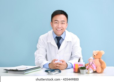 Handsome pediatrician doctor with teddy bear in office