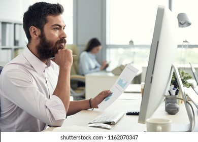 Handsome pensive entrepreneur working with documents and analyzing data on computer screen
