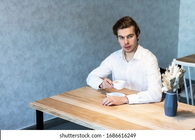 Handsome pensive male in white shirt looking away sitting at table in cafeteria thinking about plans, caucasian guy waiting for meeting in coffee shop dreaming about idea on leisure