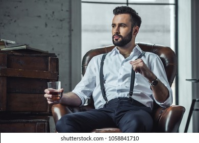 Handsome pensive man is holding a glass of whiskey and looking away while sitting in leather armchair indoors