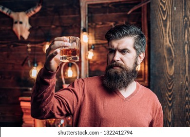 Handsome pensive man is holding a glass of whiskey. Retro bar. Man in Night club. Man drinks a cocktail. Bearded man sitting at bar