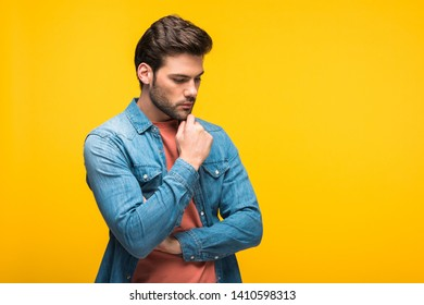 handsome pensive man touching chin Isolated On yellow with copy space
