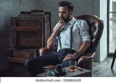 Handsome pensive man is touching his beard, looking away and thinking while sitting in leather armchair indoors