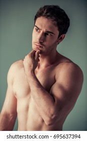 Handsome pensive young man with bare torso is rubbing his chin, looking away and thinking, on gray background
