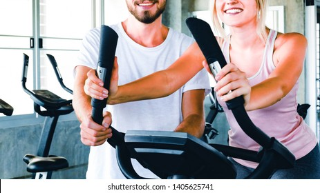 Handsome personal trainer with attractive young fitness girl coaching cardio training by bike in professional gym. Healthy, fitness,good health,fit and firm concept.