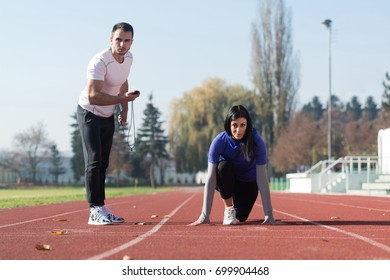Handsome Personal Trainer Helping Woman To Sprint on the Running Track in City Park Area - Training and Exercising for Endurance - Healthy Lifestyle Concept Outdoor