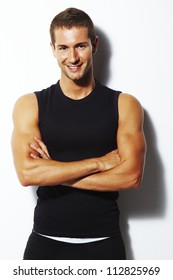 Handsome personal trainer. Strong and smiling man with crossed arms over white background