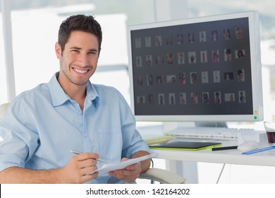 Handsome photo editor holding documents in his office