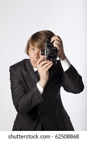 Handsome photographer in studio, ready to use his old film camera. See more in my portfolio