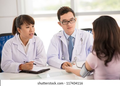 Handsome physician and his nurse diagnosing a young female patient